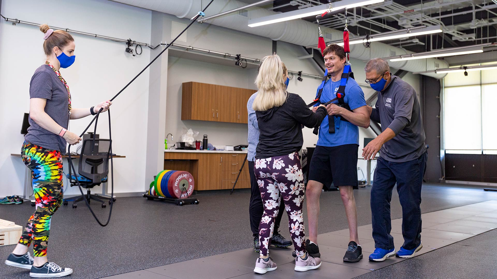 Sean Carter practices walking in a harness, supported on the right by HHPI Clinical Director Dr. Joe Hazzard, and guided by graduate students in UHCL's Exercise Sciences program.