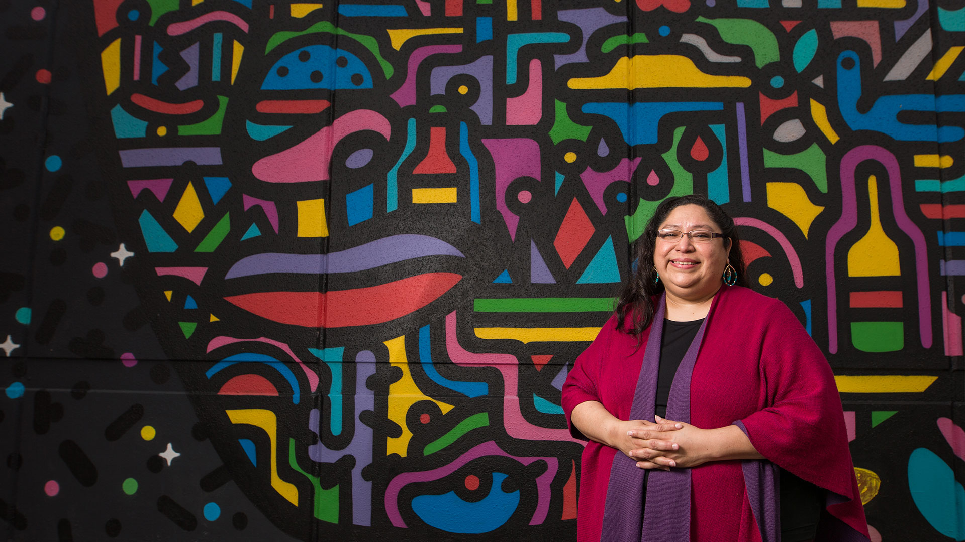 A faculty member in front of a painted mural