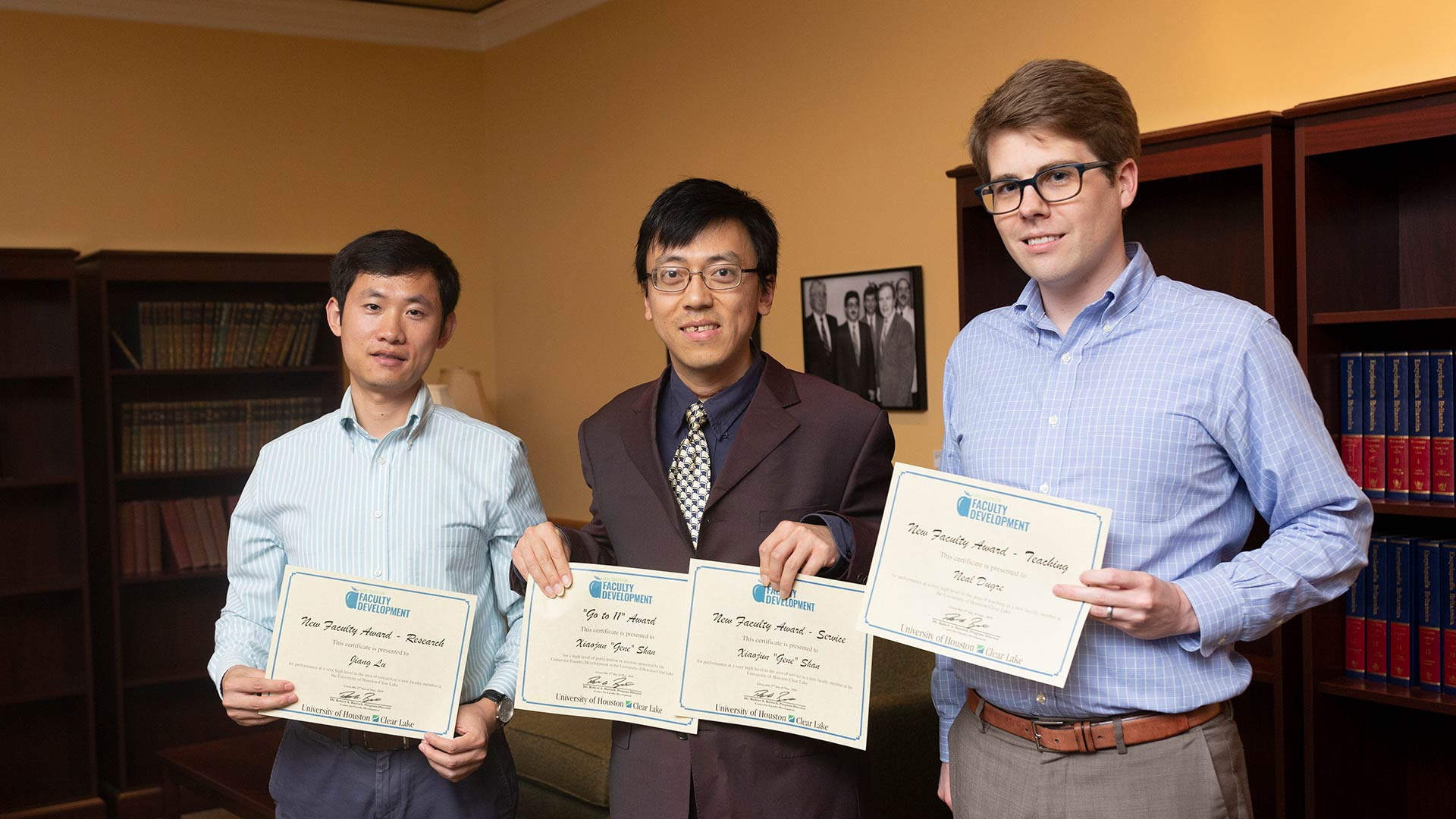 Three faculty members holding certificates